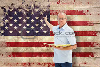 Composite image of teacher holding book and pointing