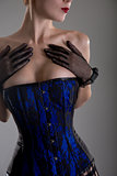 Close-up shot of busty burlesque woman in black and blue corset
