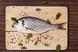 Fish on wooden board with herbs and spices.