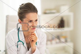 Portrait of thoughtful doctor woman in office