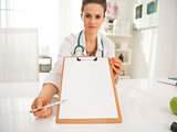 Closeup on doctor woman pointing on clipboard