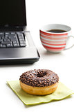 break in the  office . doughnut on laptop keyboard