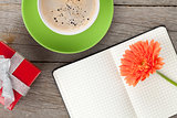 Blank notepad, coffee cup and orange gerbera flower
