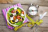 Fresh healthy salad and measuring tape on wooden table