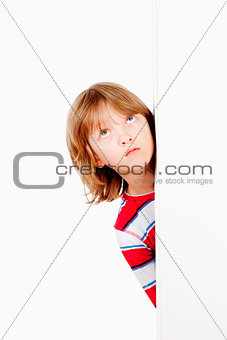 Boy Peeking Out From Behind A White Board Looking Up