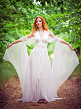 Beautiful redhead elf woman wearing white dress in a garden