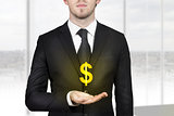 businessman holding golden dollar symbol