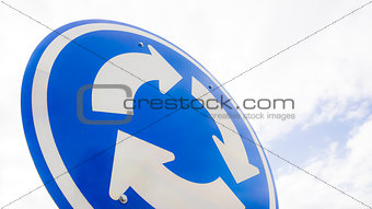 Blue road sign with arrows in a circle against sky