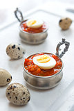 Hard boiled quail eggs with tomato sauce
