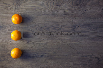 Three Oranges are on empty dark Wooden Table