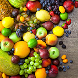 Mix of  Organic Fruits  with water drops on dark wooden table