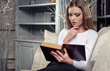 Beautiful woman reading a book indoors