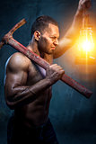 Muscular man holding pickaxe and oil lamp