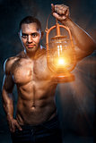 Muscular build man holding oil lamp