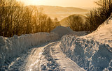 Snowdrifts and rural road at sunrise