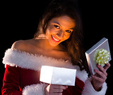 Pretty brunette in santa outfit opening gift and smiling at camera