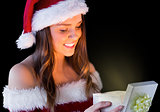 Pretty brunette in santa outfit opening gift