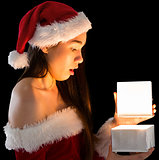Pretty brunette in santa outfit opening a gift
