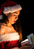 Amazed brunette in santa outfit opening a gift