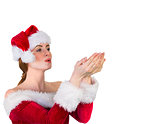 Pretty redhead in santa outfit blowing over hands