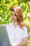 Pretty redhead using her laptop in the park