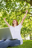 Pretty redhead using her laptop in the park and cheering