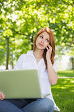 Pretty redhead using her laptop while phoning in the park