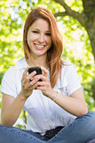 Pretty redhead sending a text in the park