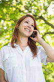 Pretty redhead on the phone in the park