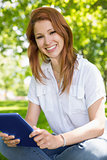 Pretty redhead using her tablet pc in the park