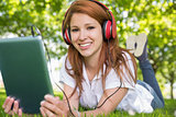 Pretty redhead using her tablet pc while listening to music in the park