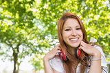Pretty redhead listening to music in the park