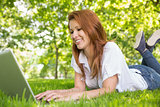 Smiling redhead using laptop in the park