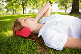 Pretty redhead lying on grass listening to music