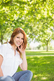 Pretty redhead smiling at camera in the park