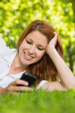 Pretty redhead lying on the grass sending a text