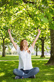 Pretty redhead raising her arms in the park