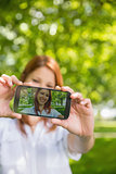 Pretty redhead taking a selfie on her phone in the park