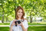 Pretty redhead holding her camera in the park