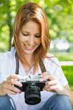Pretty redhead looking at her camera in the park