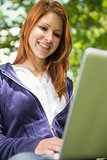 Pretty redhead relaxing in the park using laptop