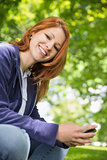 Pretty redhead relaxing in the park sending a text