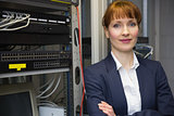 Pretty computer technician smiling at camera beside server