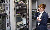 Pretty computer technician talking on phone beside open server
