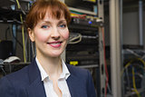 Pretty computer technician smiling at camera beside open server