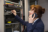 Pretty technician talking on phone while fixing server