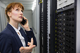Pretty technician talking on phone while looking at server