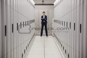Serious technician standing in server hallway