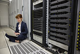 Technician sitting on floor beside server tower using laptop