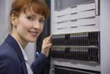 Pretty technician smiling at camera beside server tower